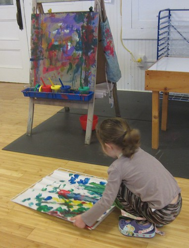 carefully setting her painting on the drying rack