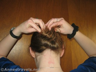 Twist the remaining hair down into the center of the oval while making a Hair Elastic Twist Up - 12 Hiking Hairstyles that are Pretty & Practical