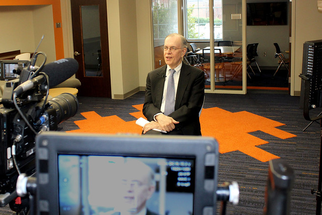 Auburn Professor James Barth sits in front of a TV camera.