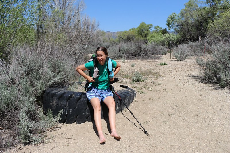 Sitting down on an old tire to dry out our feet after crossing Cottonwood Creek