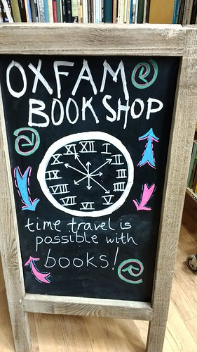 chalkboard illustration of a clockface with extra hands, spirals and arrows - time travel is possible with books