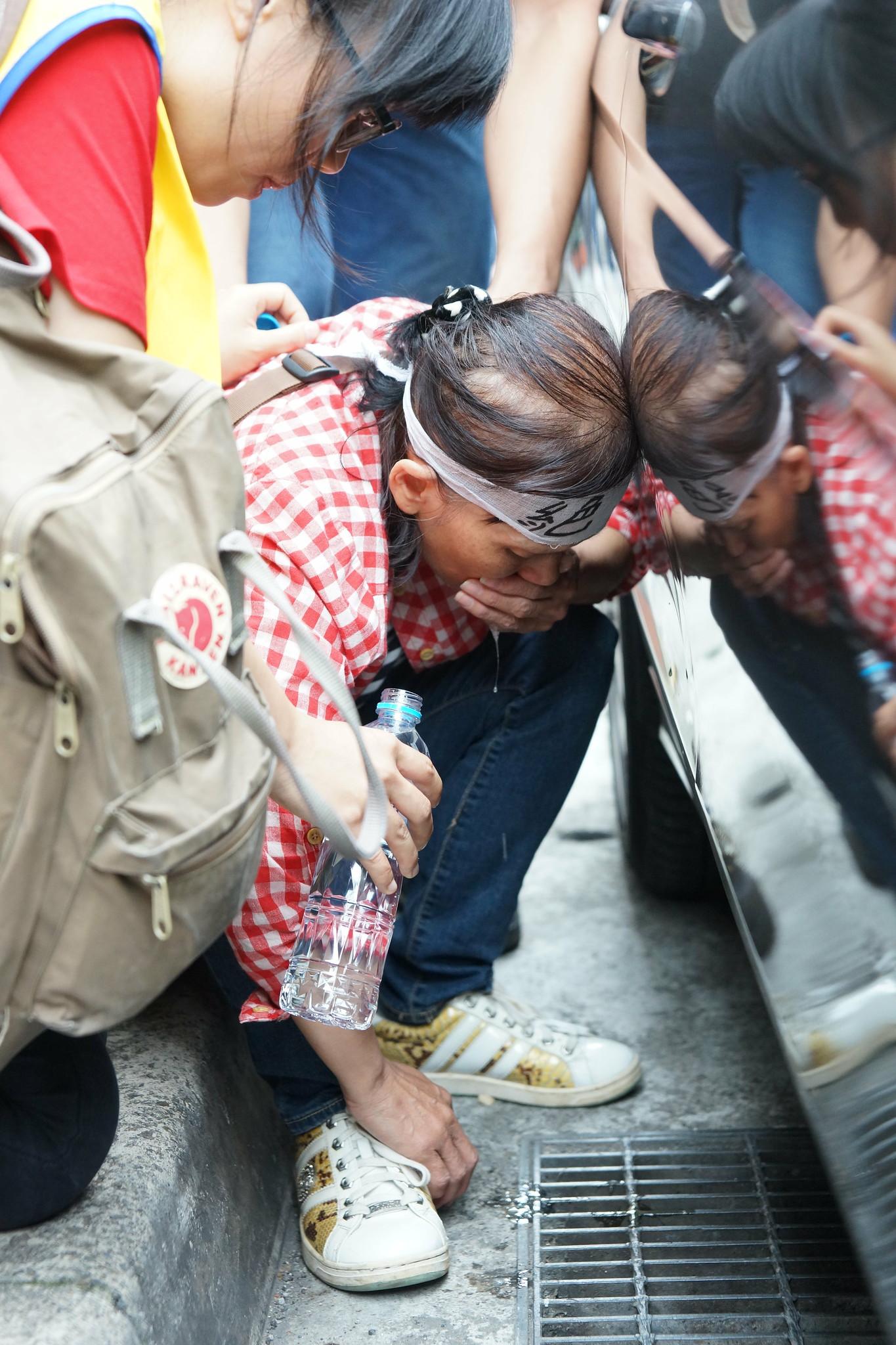 絕食邁入第五天的三名絕食女工上午也一同北上,58歲的陳美秀在行動過程中幾度體力不支,必須仰賴其他工會幹部攙扶至路邊乾嘔。(攝影:王顥中)
