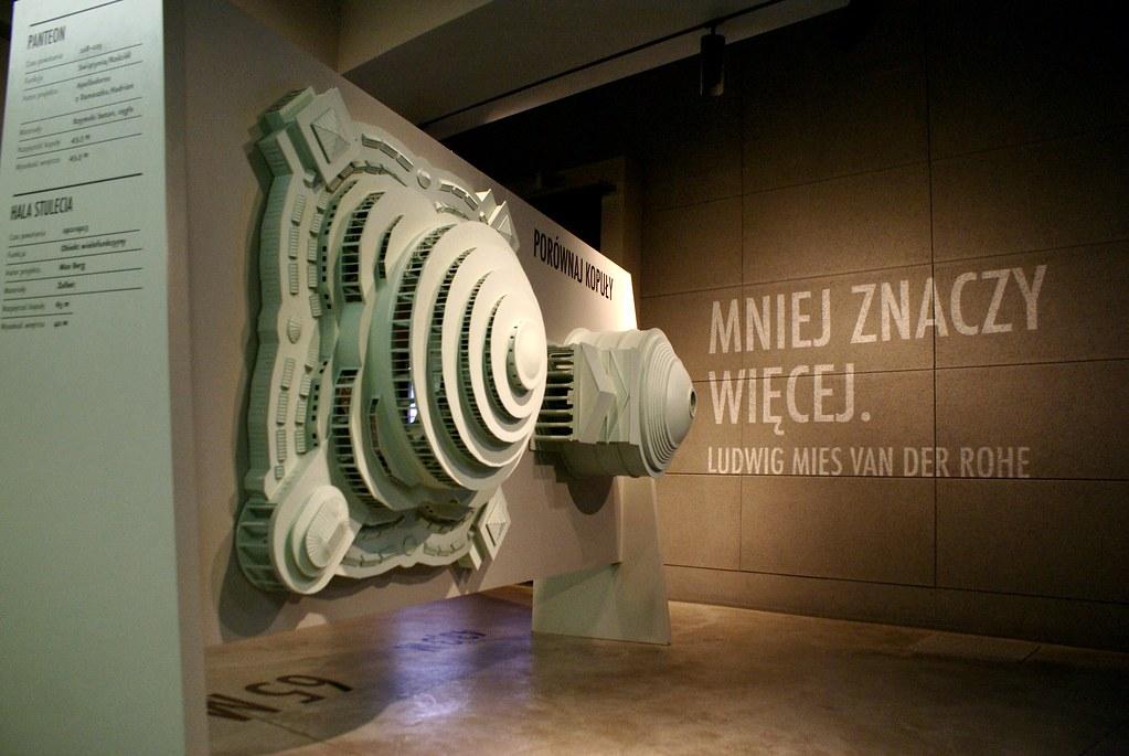 """Panthéon et Halle du centenaire devant la citation de Mies Van Der Rohe """"Less is more"""". Dans le musée de la Halle de Wroclaw."""