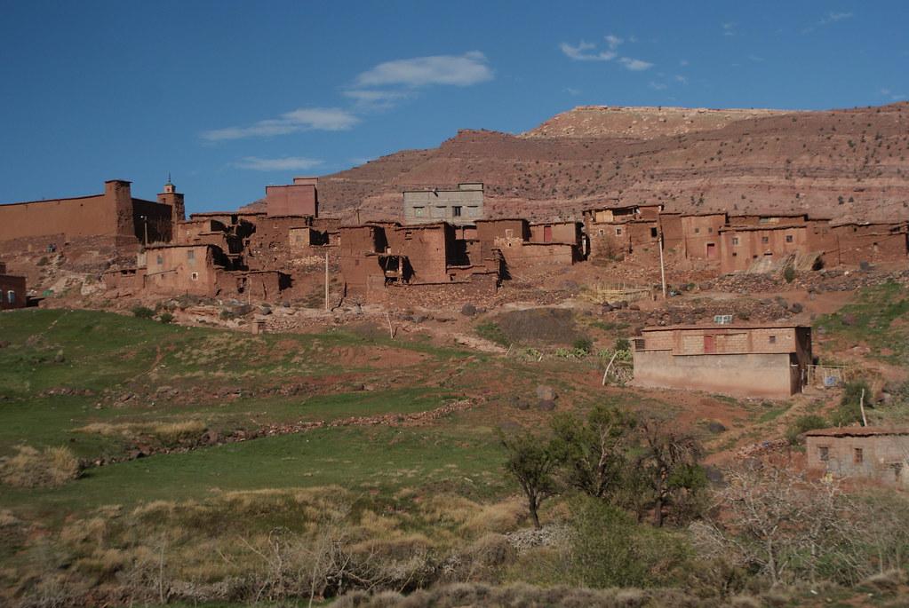 Village marocain en terre se fondant dans le paysage le long d'une rivière de montagne.