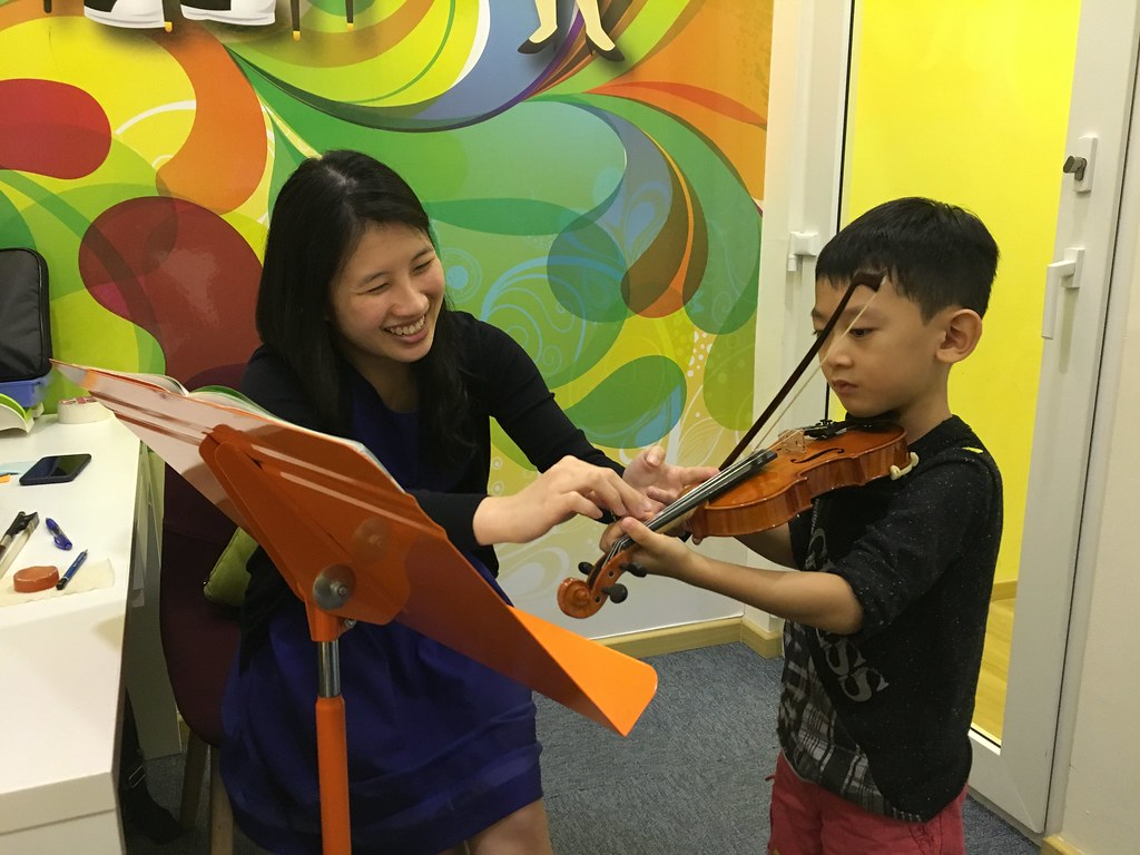 The always-cheerful Ms Alice Wong showing Asher how to use his fingers on the E string.