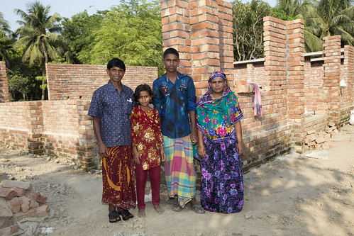 A family stands by the construction of their new house in Jessore, Bangladesh. Photo by M. Yousuf Tushar.