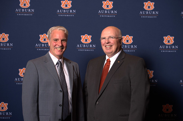 Dan LaRocque and Timothy Boosinger pose for a portrait in front of an Auburn University backdrop.