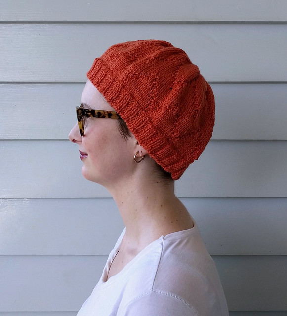 A woman wears a handknit, pumpkin coloured hat and white tee.