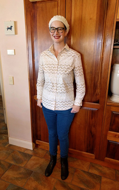 A woman wears a cream hand-knitted beret, geometric print button up shirt, skinny blue jeans and brown ankle boots.