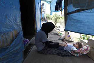 Fatatima plays with her son, Mouath in their makeshift home in the Ketermaya refugee camp | by World Bank Photo Collection