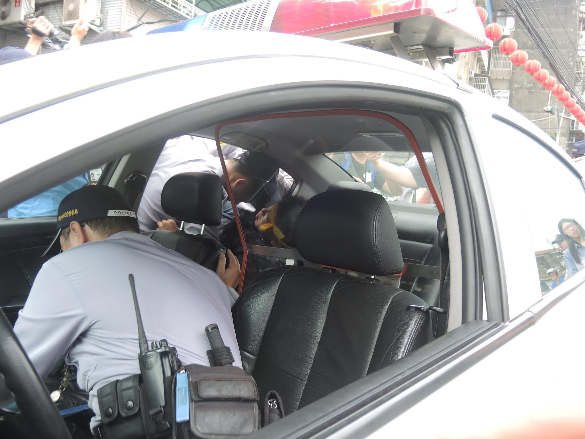 聲援者鄭仲皓隨即遭強押上巡邏車,帶回警備車內拘禁。(攝影:曾福全)