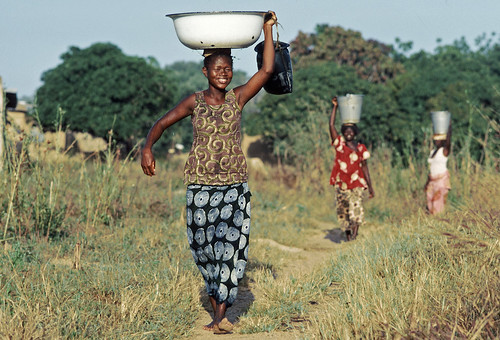 Smiling village women from Ouagadougou, Kadiogo, Burkina Faso returning home from a community well with containers full of water.