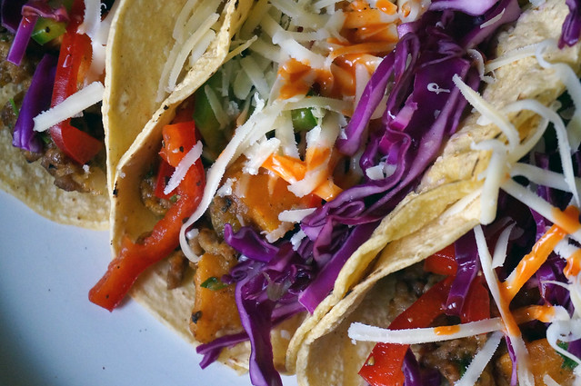 Closeup on the combined fillings, a tangle of red, green, purple, and ivory resting in a pale yellow tortilla.