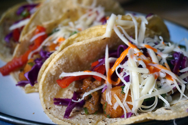 Sweet potato tacos with marinated peppers and cabbage on a plate, the nearest one falling seductively open to reveal a riot of colors and textures within.