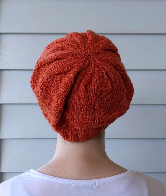 A close-up image of the back of a young woman against a blue weatherboard wall. She wears an orange hand-knitted hat and a white tee.