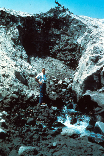 Color image shows a tall mound of volcanic debris with a cirque-like channel carved in it. Water is gushing from the talus three-quarters of the way down. A man in jeans and a t-shirt is standing beside the spring, looking toward the camera with his hands on his hips.