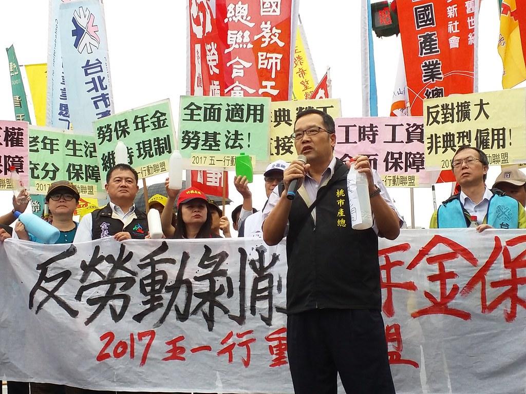 五一行動聯盟總指揮莊福凱用手上的瓶罐諷刺「慣老闆」,批評台灣慣老闆剝削勞工。(攝影:張智琦)