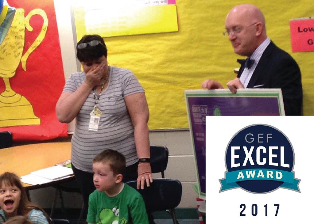 Teacher surprised by large check in classroom with logo and text 'Excel Award 2017'
