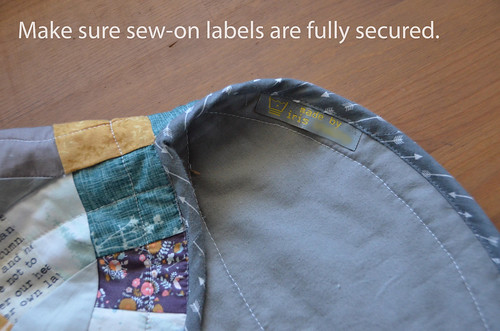 8. Make sure any sew-on labels are properly placed when you sew the binding over them.