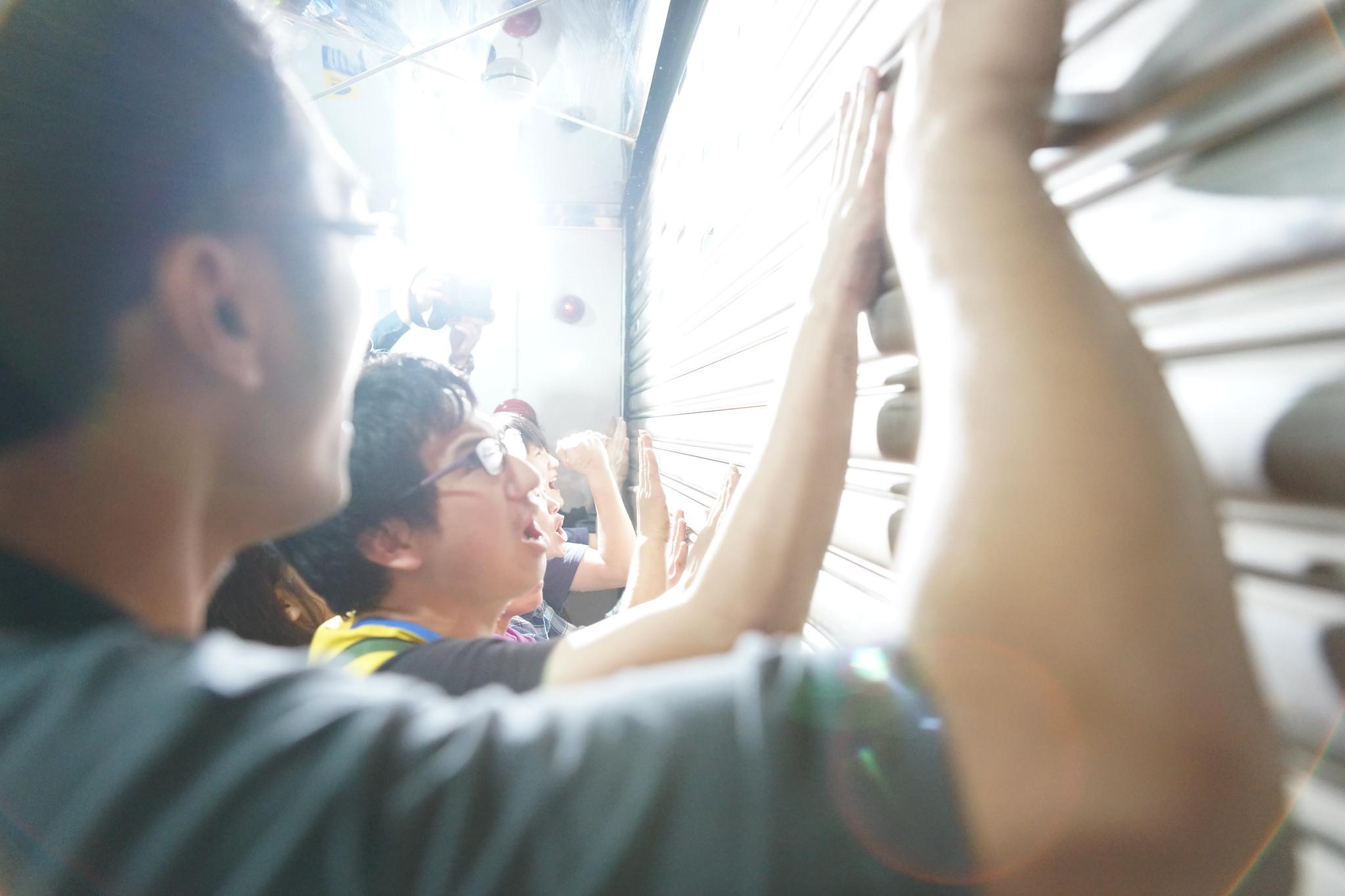 工會只能一面拍打鐵門,一面呼喊「蘇東榮出來」。(攝影:王顥中)