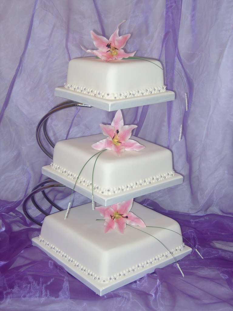 3 tier square wedding cake with lillies on stand cakes by shelly