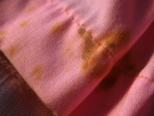 stained dress material on old doll