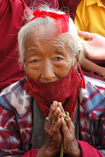 Elder Tibetan woman praying wearing face mask to protect against the dust, and symbolic red blindfold, during Lam dre, Tharlam Monastery, Boudha, Kathmandu, Nepal | by Wonderlane
