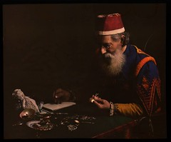 Costumed man examining jewelry (pawnbroker?) | by George Eastman Museum