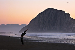 "Upward Salute – Urdhva Hastasana - Person performs mystical ""Sun Salutation"" yoga stretching exercise on Morro Strand ""Church of Kelp"" 