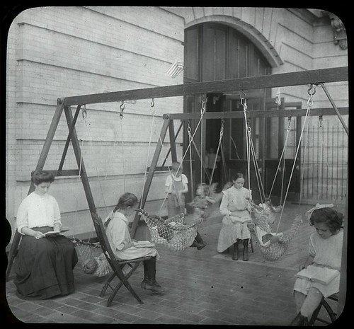Women and girls reading near swingset where younger children... | by New York Public Library