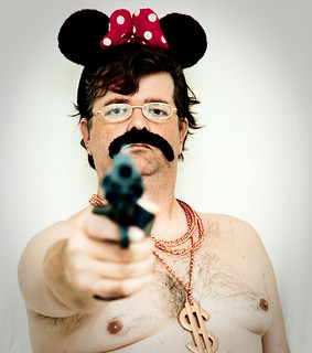 About a Man, a Mouse, a Gun, a Moustache, Some Gold Chains, a Pair of Glasses, and a Polkadot Bow | by TrEjAcK