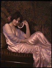 Woman in satin dress holding mirror | by George Eastman House
