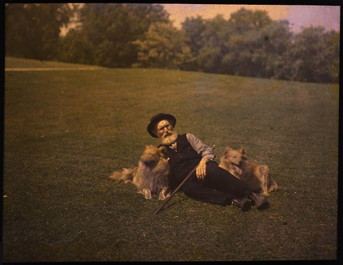 Man lying on ground with two dogs | by George Eastman House