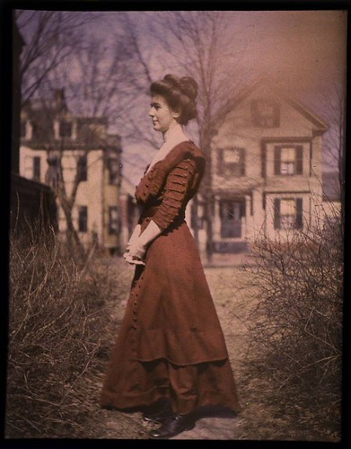 Woman wearing red dress with houses in background | by George Eastman Museum