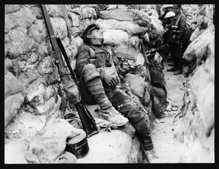 Soldier's comrades watching him as he sleeps, Thievpal, France, during World War I | by National Library of Scotland
