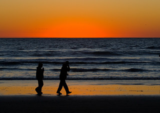 Couple walk in silhouette on Morro Strand State Beach | by mikebaird