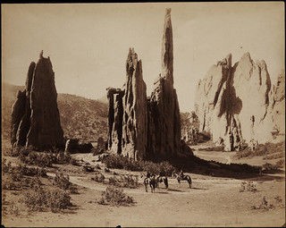 [No. 1183. A individuals sit on horseback in the Garden of the Gods near sandstone rock formations identified as Cathedral Spires, Colorado Springs (El Paso County), Colorado. Shows a dirt road and trees]. | by Beinecke Library