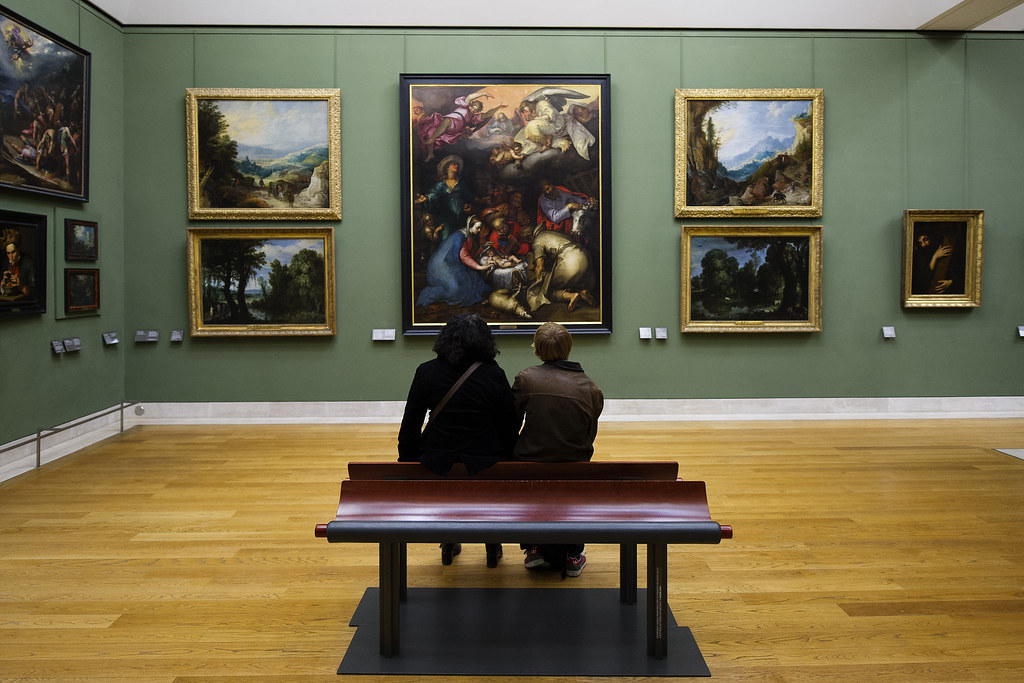 An image of people appreciating paintings in a museum