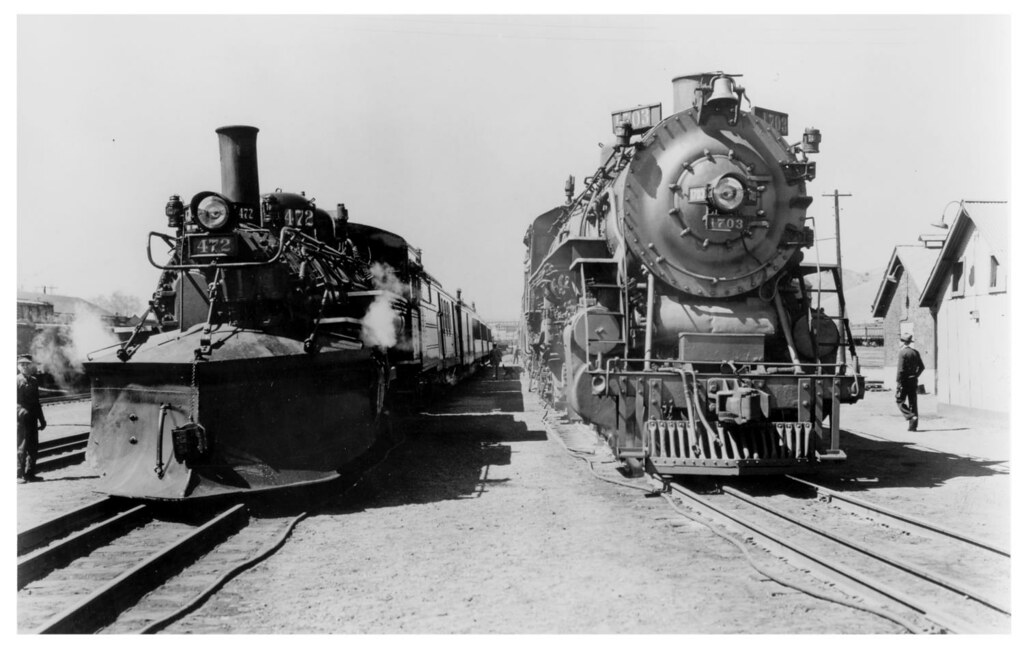 Denver & Rio Grande Western narrow gauge Alamosa-Durango train with a 2-8-2 on the left and standard gauge Denver-Alamosa train on the right with a 4-8-2 in Alamosa in 1943