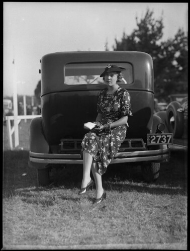 Woman sitting on bumper bar of a car at Warwick Farm racecourse | by Powerhouse Museum Collection