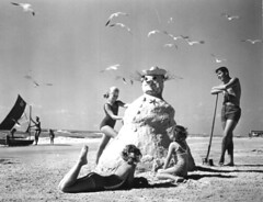 "Three girls making a ""sandman"" at the beach 