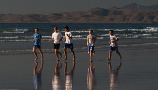 Five high school boys, as part of a larger group, run up and down the beach | by mikebaird