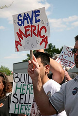"Supporters at Saginaw, MI rally holding ""Build Here Sell Here"" and ""Save America"" signs 