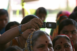 Woman takes photo with cellphone at a community meeting | by World Bank Photo Collection