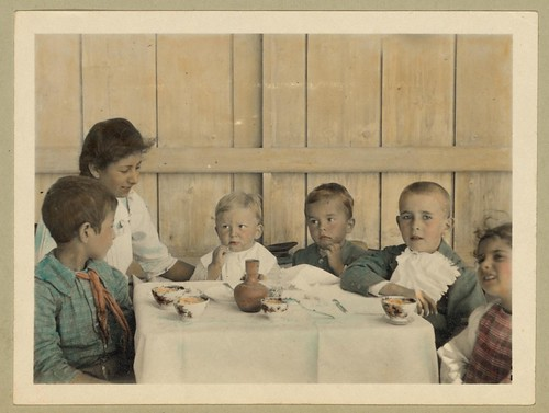Vintage Picture of Children Sitting Down at a Table about to Eat a Meal, Boys, Girl, Woman | by Beverly & Pack
