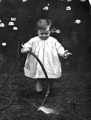 Toddler playing with a hose in a garden | by State Library of Queensland, Australia