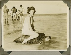 Young woman riding on the back of a turtle at Mon Repos Beach | by State Library of Queensland, Australia
