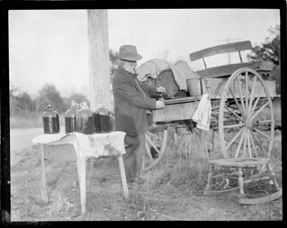 Man operates still out of the back of a carriage | by Boston Public Library