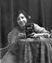 Young smiling woman, holding a camera | by State Library and Archives of Florida