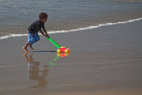 Mowing Water! Youngster with plastic lawn mower toy playing in the wet sand at water's edge on Morro Strand State Beach | by mikebaird